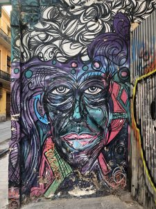 A graffiti street piece of a portrait. Lots of purples and blues and greens to create this eclectic character