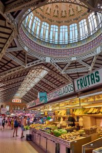 mudarse a El Carmen - inside the central market in Valencia. Here you can see the beautiful glass ceiling and art nouvou styled interior. There are fruit and vegetable stands selling watermelons, bananas, potatoes and various other fresh produce.